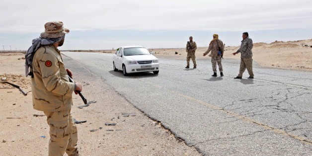 Libyan soldiers manning a military outpost, stop a car at a checkpoint in Wadi Bey, west of the city of Sirte, which is held by Islamic State militants